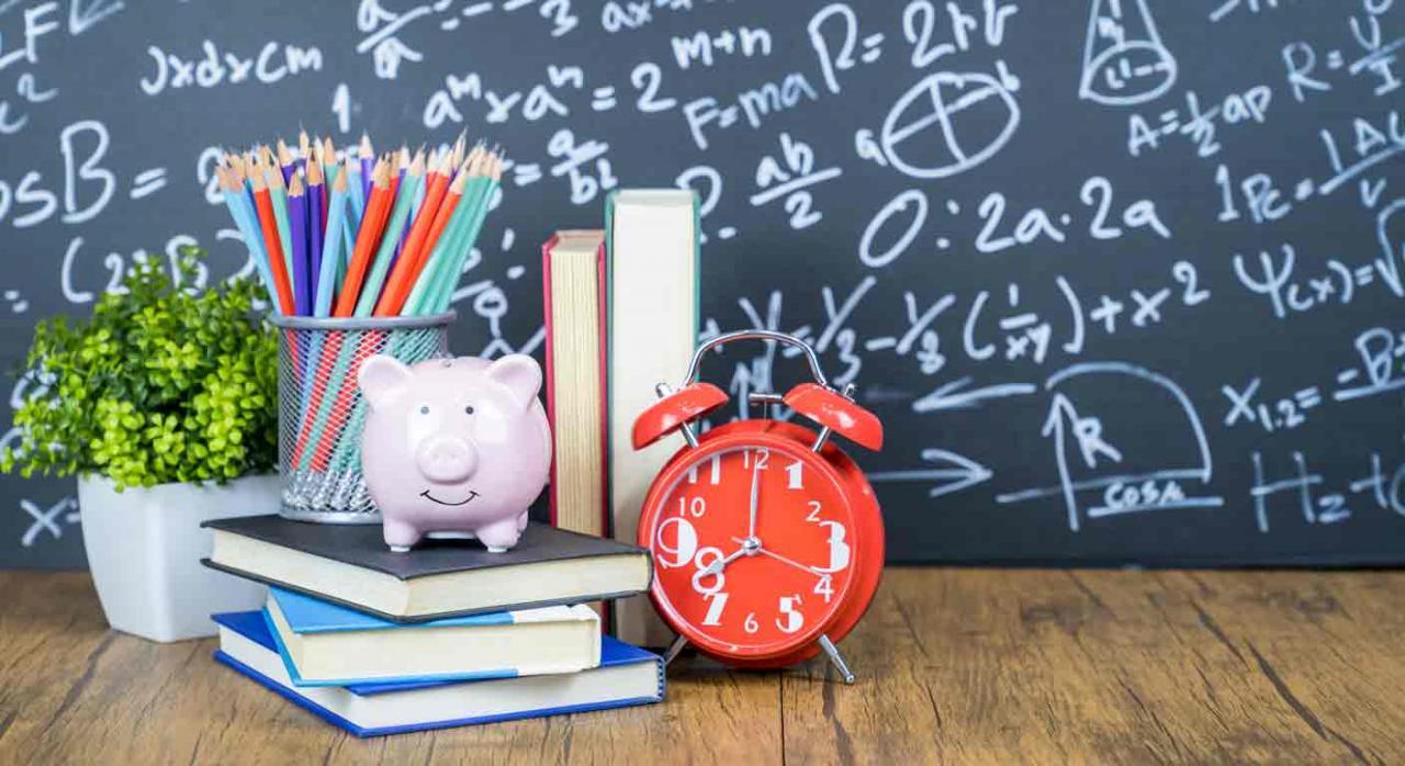 Deducción gastos educativos. Un pizarra, libros apilados, un portalápices lleno, un despertador y una hucha