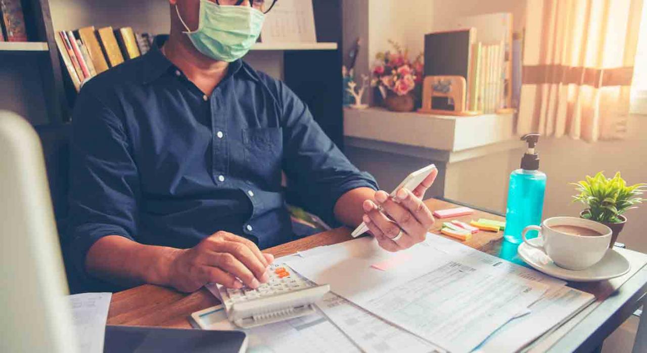 IRPF, IP, 2020, campaña, renta, ERTE. Un hombre usando una calculadora con muchos papeles sobre la mesa