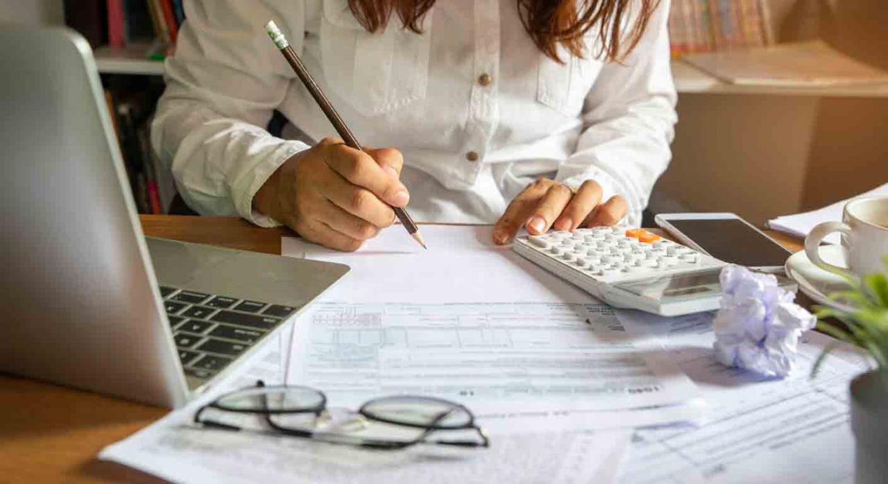 Recomendaciones, ahorro, IRPF, 2020. Mujer haciendo cálculos sobre una mesa con una calculadora, unas hojas y un portátil