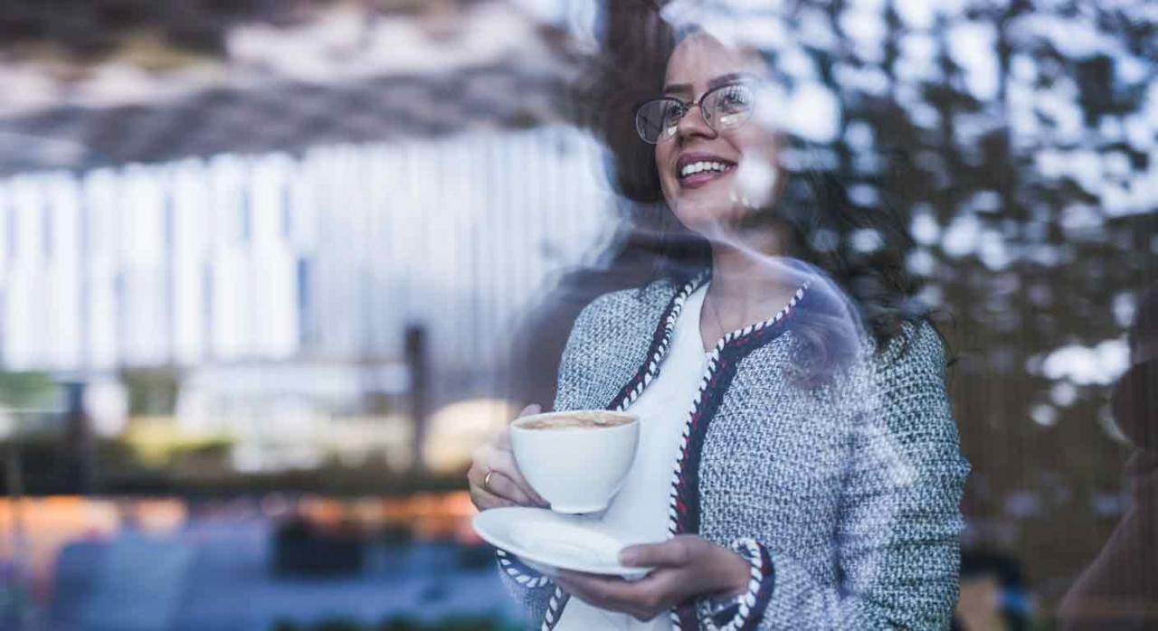 Plazos ampliados. Imagen de una empresaria con un café en la mano mirando a través de una ventana