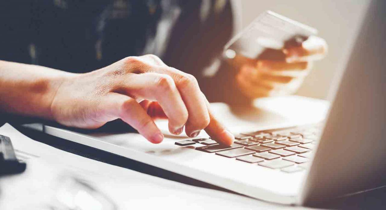 Pago entidades colaboradoras. La mano de un hombre sobre las teclas de un portátil y una tarjeta de crédito en la otra