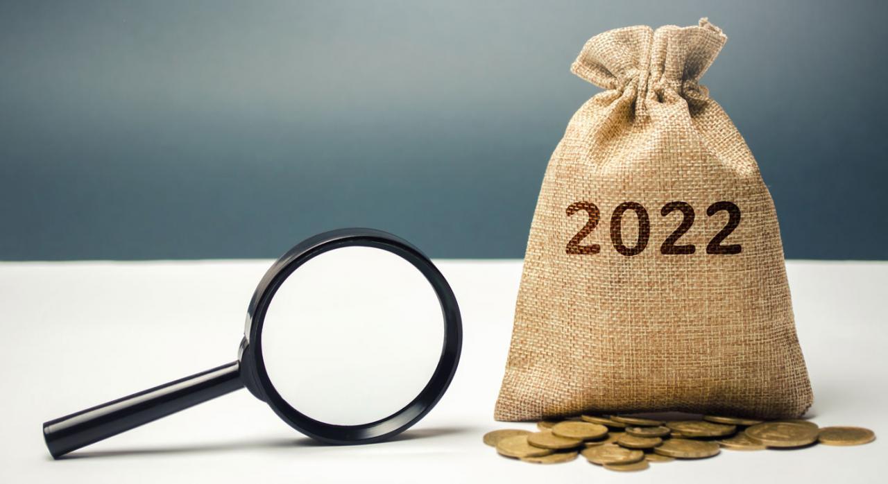 Proyecto de Ley de PGE para 2022: Medidas fiscales . Imagen de un saco con el 2022 y monedas debajo y una lupa