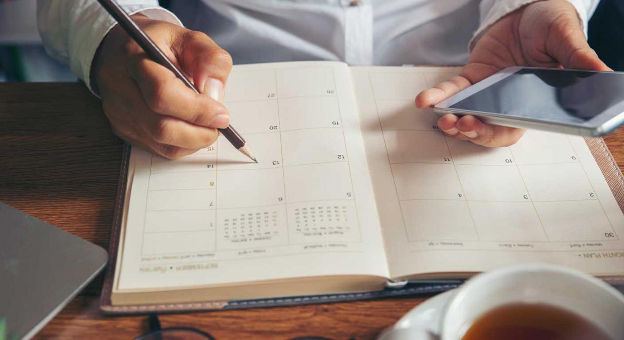 Madrid plazos. Imagen de una mano de una persona anotando cita en una agenda y el móvil en la otra mano