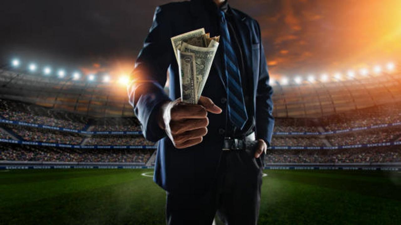 El Real Madrid no puede deducirse el IVA de los agentes de los futbolistas. Imagen de ejecutivo en pie sobre el campo de futbol con dinero en efectivo en la mano
