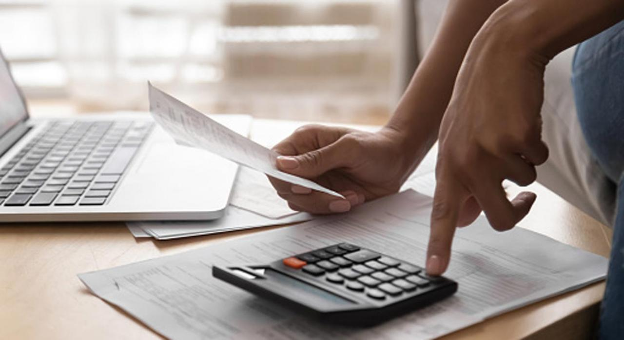 TS: Hacienda debe resolver el recurso de reposición pendiente antes de apremiar la liquidación. Imagen de dos personas con una calculadora y papeles sobre una mesa