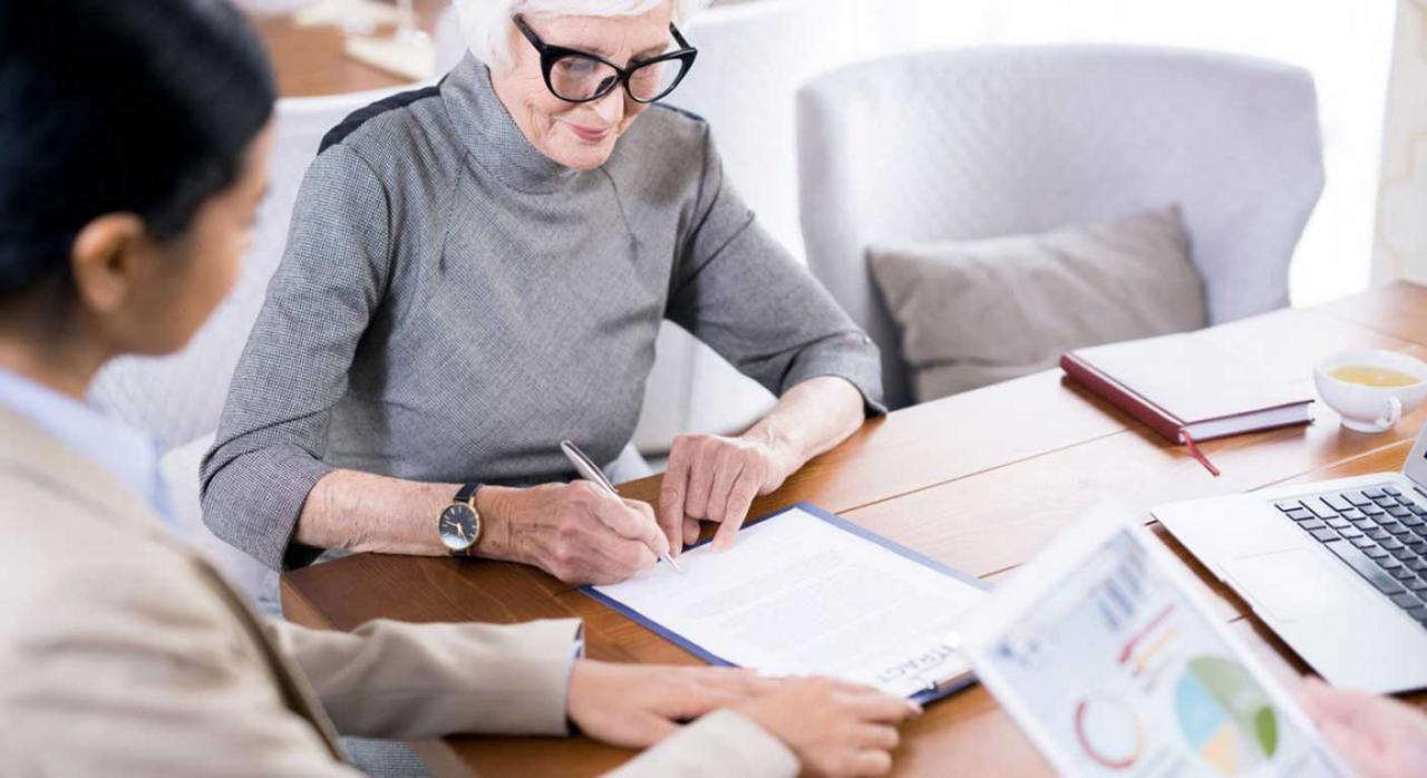 reducción 40% planes pensiones. Imagen de una mujer firmando documentos