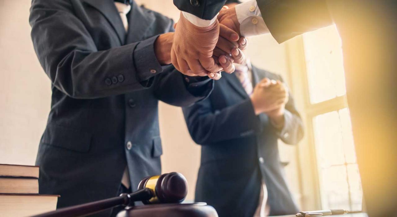 Reducción del 30% sobre la retribución obtenida por un litigio ganado. Dos hombres estrechándose la mano frente a un mazo de juez