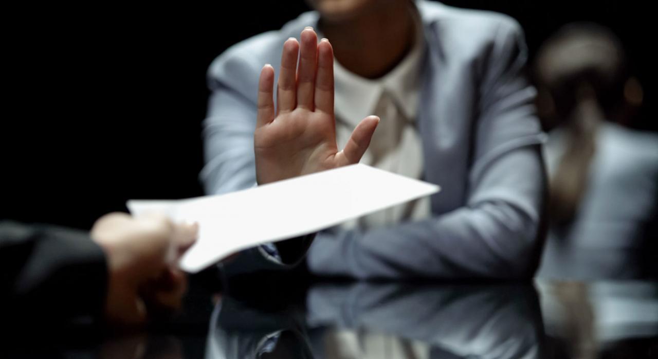 La Administración ha de motivar la negación de los datos fiscales proporcionados. Imagen de un señor negando un papel que le están ofreciendo