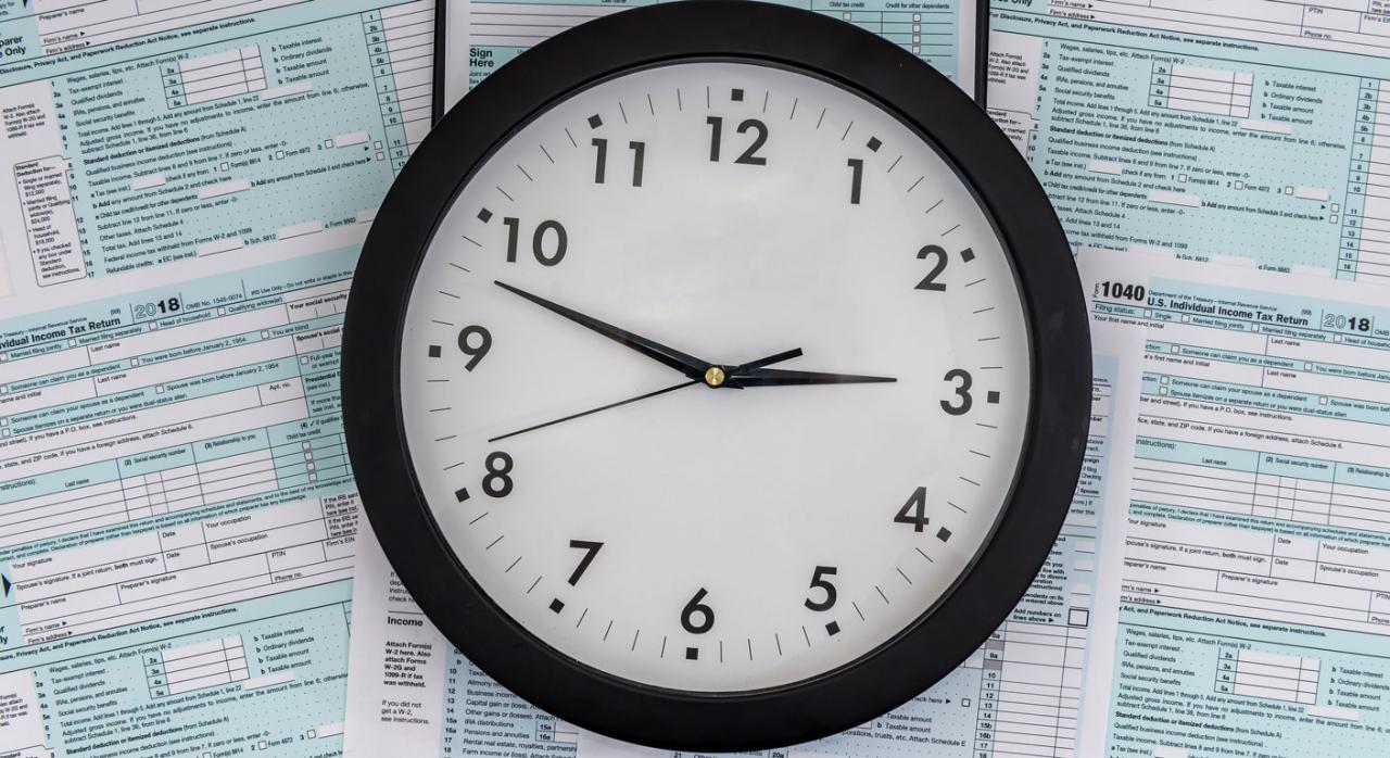 Imagen de un reloj sobre formularios de sancion agente tributario
