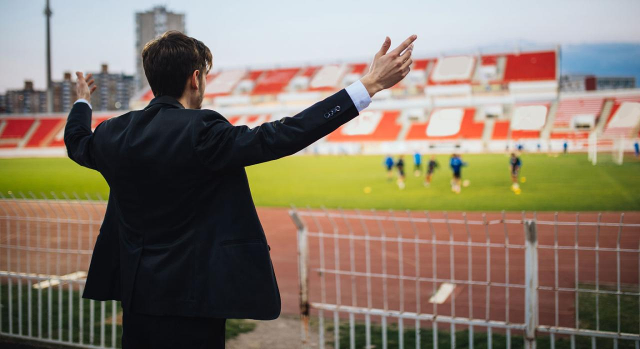 Residencia fiscal entrenador de futbol de espaldas frente a un estadio
