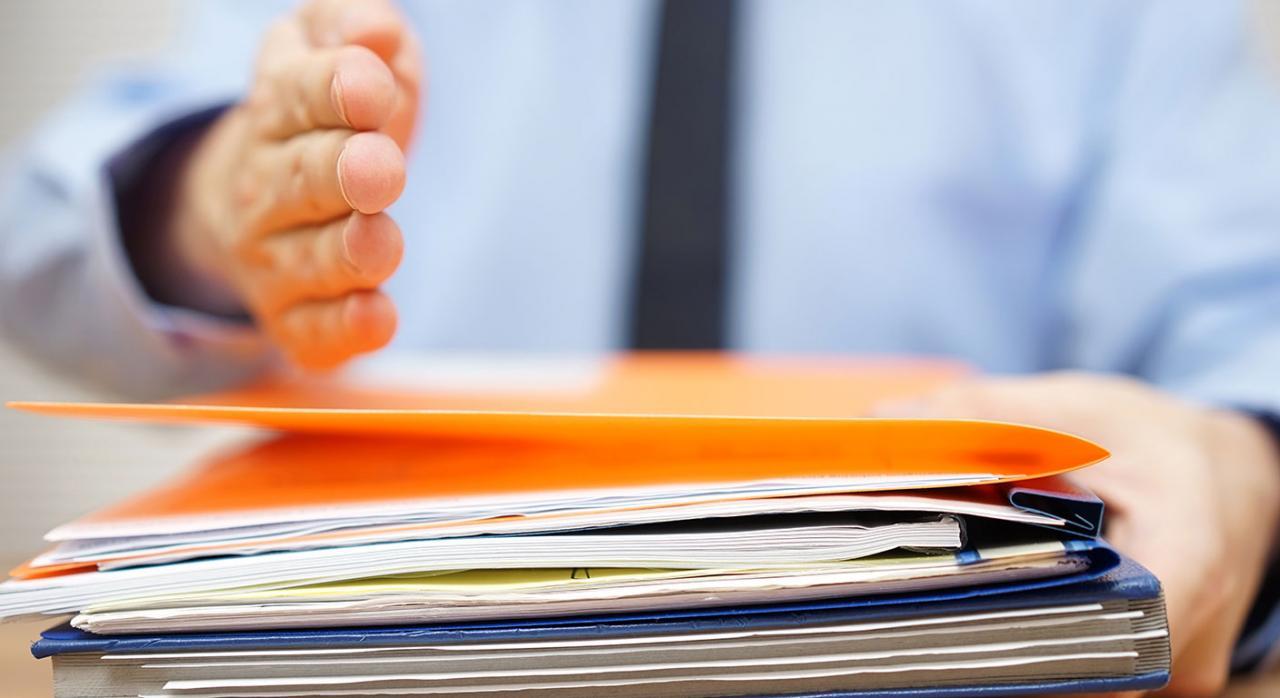 Responsables subsidiarios, aplazamiento, fraccionamiento, retenciones. Imagen de la mano de un hombre sobre una carpeta con papeles