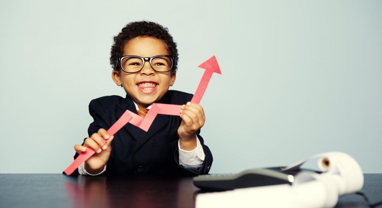 Proyectos de ley de impuestos sobre servicios digitales y transacciones financieras. Niño trajeado sonriendo y con una flecha económica en la mano