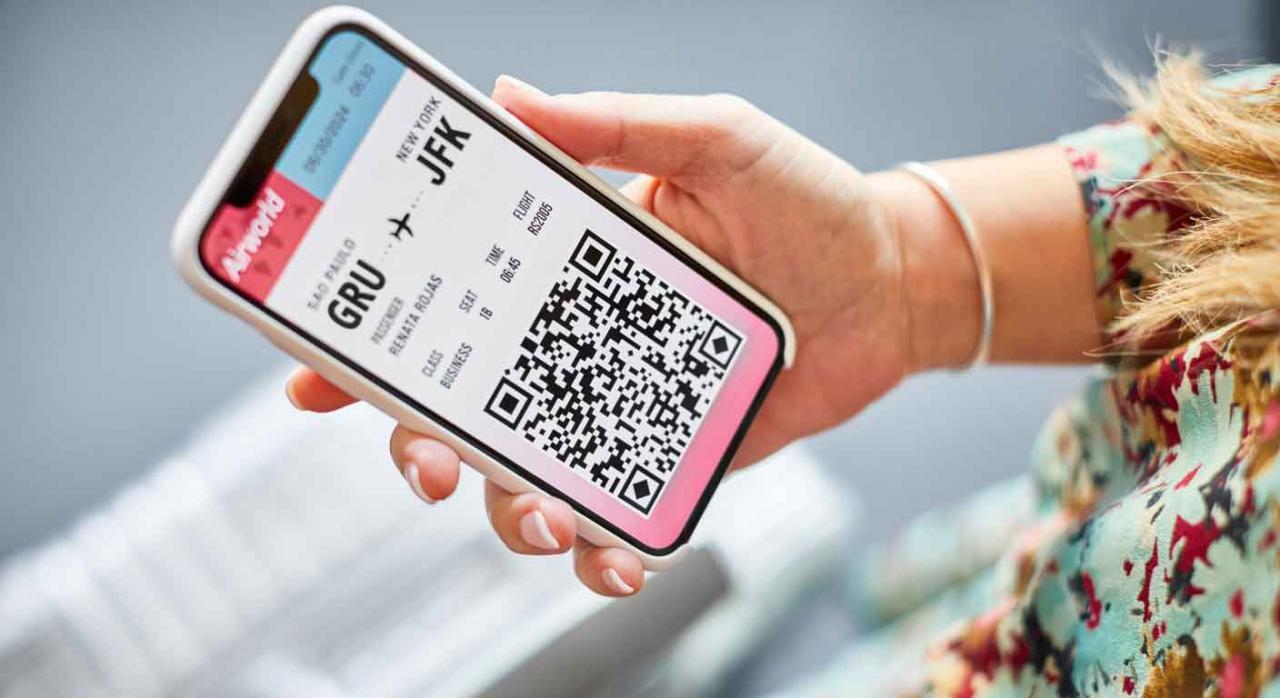 Tasa YQ IVA. Mujer sosteniendo un móvil con una tarjeta de embarque en la pantalla