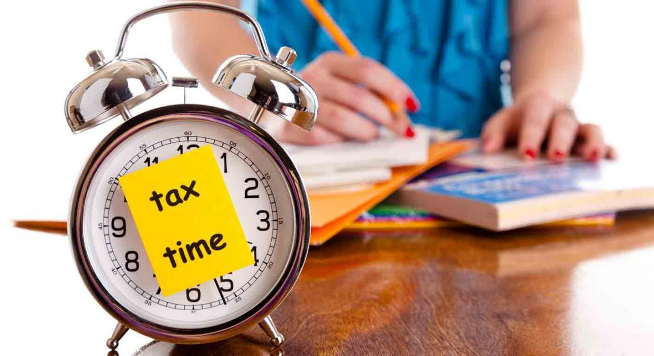 Declaraciones informativas 2020. Despertador con un posit pegado en la pantalla donde pone tax time y al fondo una mujer trabajando