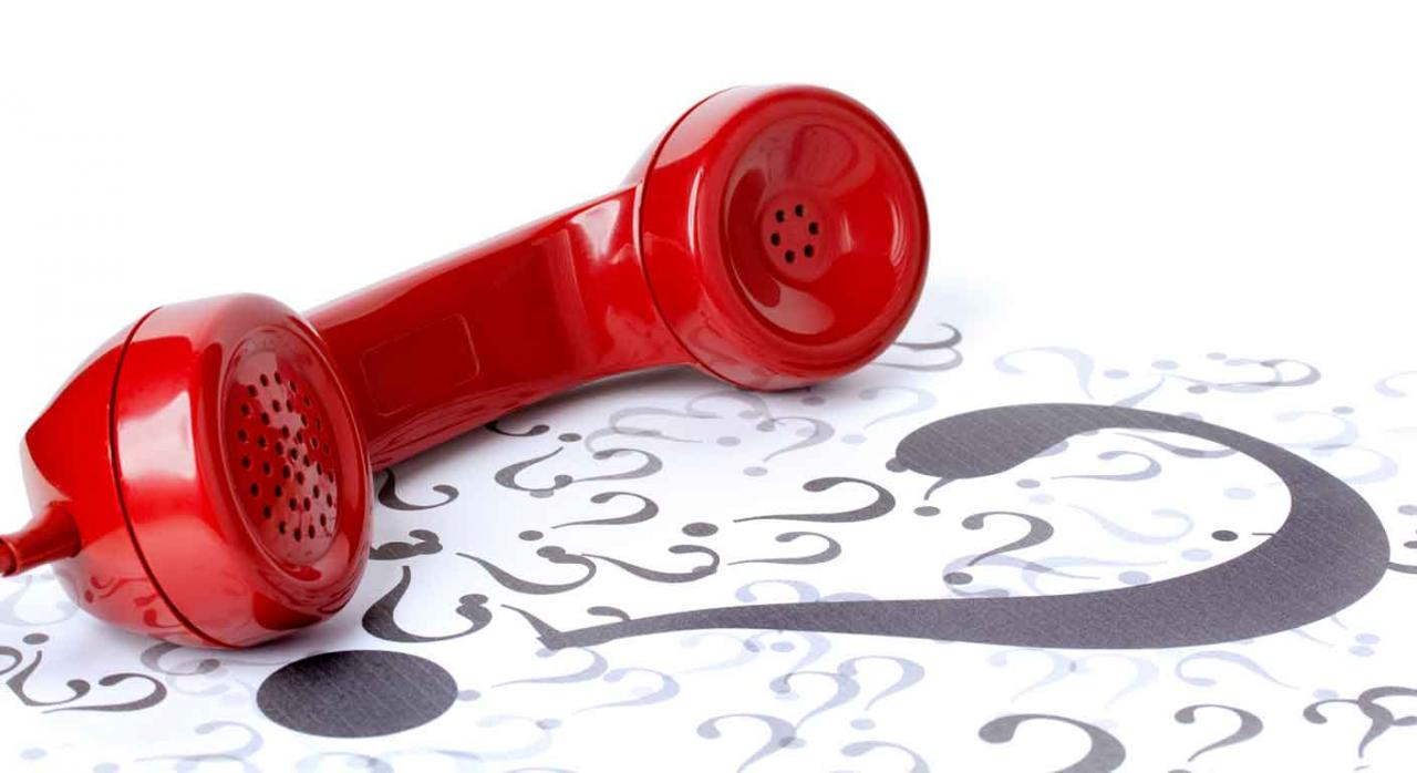 Agencia tributaria teléfono. Auricular teléfono de color rojo sobre un montón de signos de interrogación