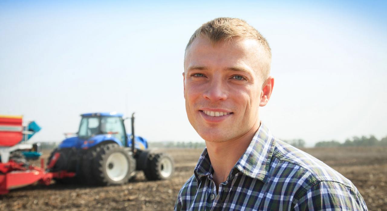 Tributación jóvenes agricultores. Imagen de un hombre joven cerca de un tractor